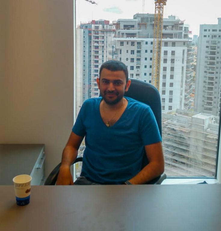 אקסלמן מומחה שירותי אקסל יושב על כיסא במשרד עם נוף של ביניינים